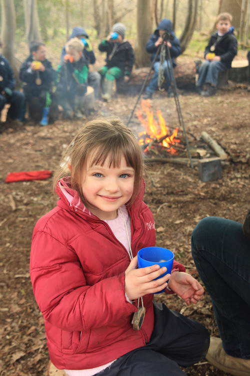 An image of a girl in front of the fire in the woods