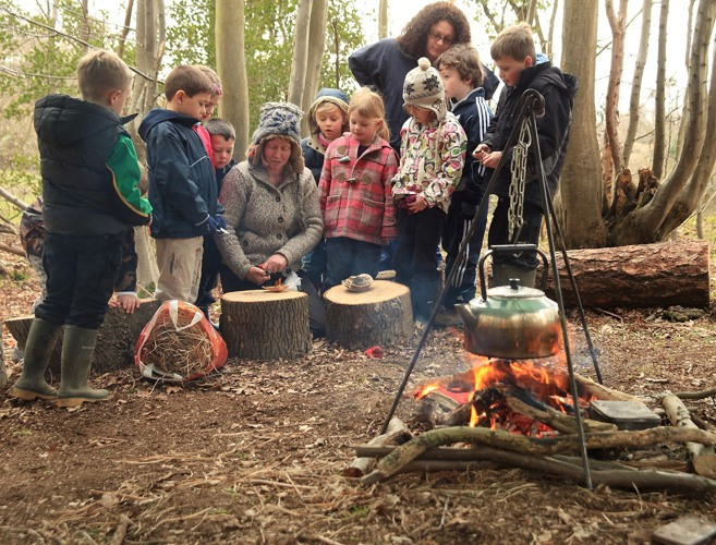 An image of children being shown how to use a fire steel around a fire in the woods at Great Dixter
